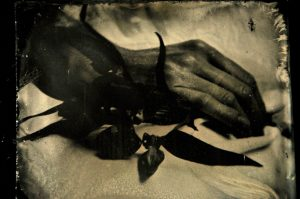 """7. Postpunctum_piasecka_5 - Aga Piasecka - """" Project """"Post -punctum"""" was inspired by 19th century post-mortem photography. I used ambrotype method to document the journey which body has to complete from the moment of death till the burial. My work is meant to question the way how the death of an individual person is depicted in contemporary visual culture. It is considered a taboo, although media bombards us with images of violent mass deaths. Photographs were taken in a funeral home in the north of Poland. To preserve anonymity of the photographed bodies and their surroundings I have chosen to use close-up to frame my images. I believe it gives more universal and ordinary outlook. Using an archaic photographic method enables me to dissolve the boundries between time, space, past, present, history and reality - I mean to achieve certain timelessness. The title of the series is derived from the Roland Barthes' essay Camera Lucida in which the author coins the term of punctum."""""""