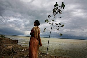 54. Climate Migrants 01 - Abir Abdullah - Puspa Rani Roy stands at the edge of her eroded land before shifted to a new land. She lived here for fifteen years with her husband, two children and mother-in-law. ' This is our own land and it will go to the river by tomorrow. I could remember many memories with my family members here. It is such a pain that we never get back this land and surely become landless like refugee.'